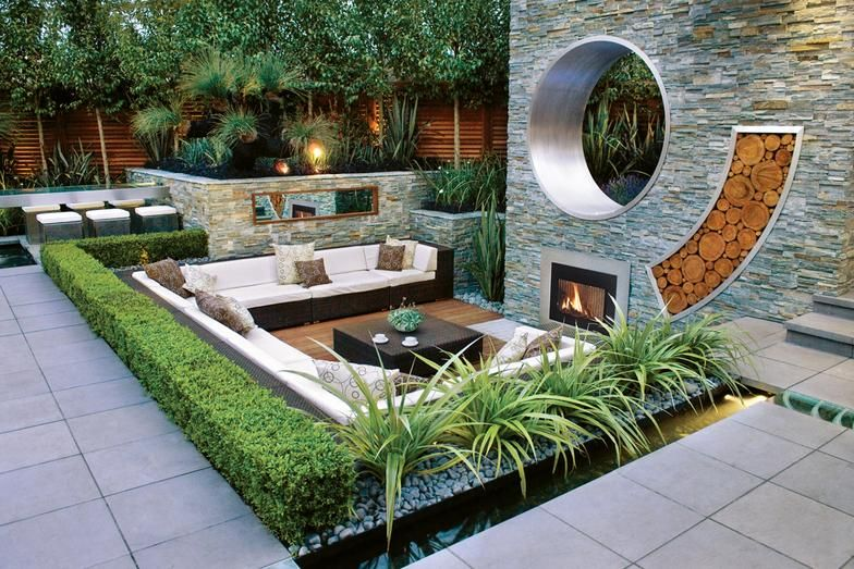 Landscape Modern Design For Backyard Garden With Wicker Sectional Sofa And Coffee Table Front Of Stone Wall Fireplace Log Accent Surrounded