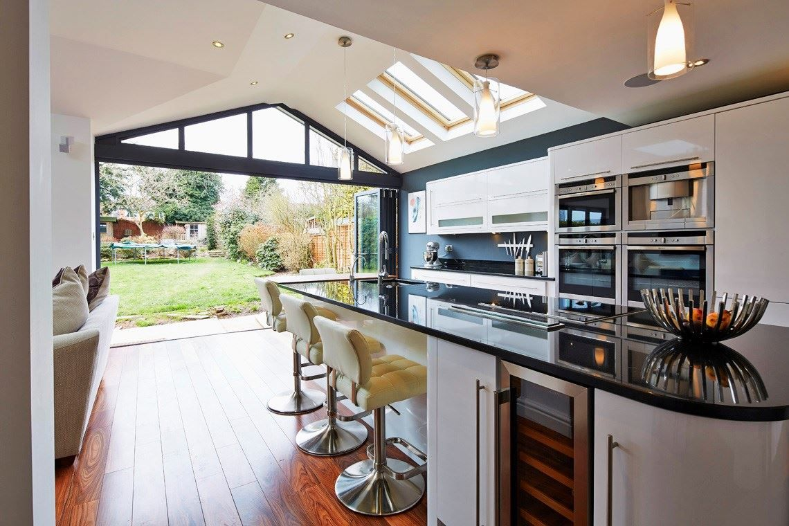 Open Plan Kitchen Looking Into A Garden Through Folding Doors
