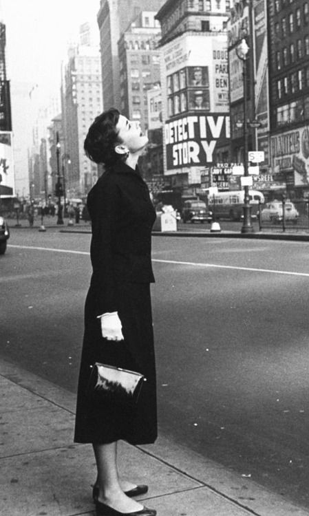 """Audrey Hepburn in New York looking up at billboards in middle of Times Square, recently in town for the Broadway show """"Gigi"""", in which she is starring. 1951"""