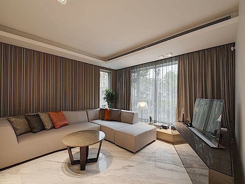 beige sofa with rounded table and brown curtain in modern living