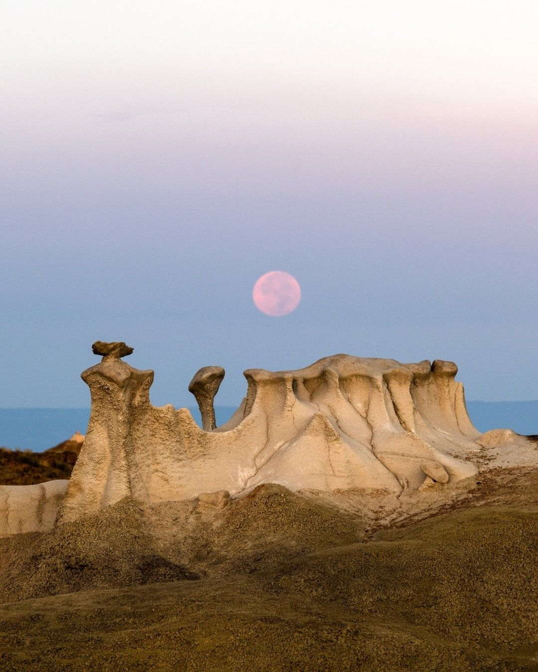 """National Geographic Your Shot on Instagram: """"Photo by @navidbaraty The autumn harvest moon sets just before sunrise over the Bisti Badlands of New Mexico. The badlands are an…"""""""
