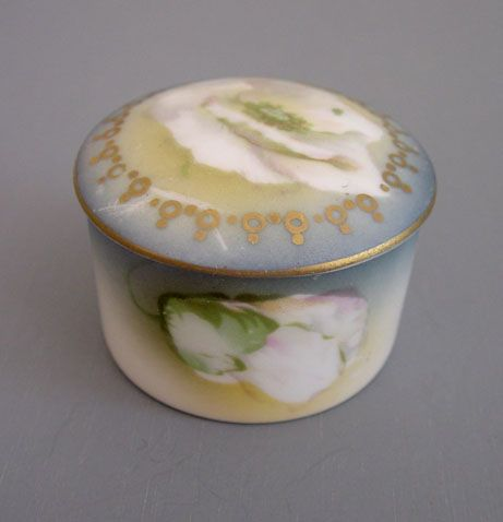 """RS GERMANY round stamp box with white wild rose design, early 1900s, 1-3/4"""" by 1-1/3""""."""