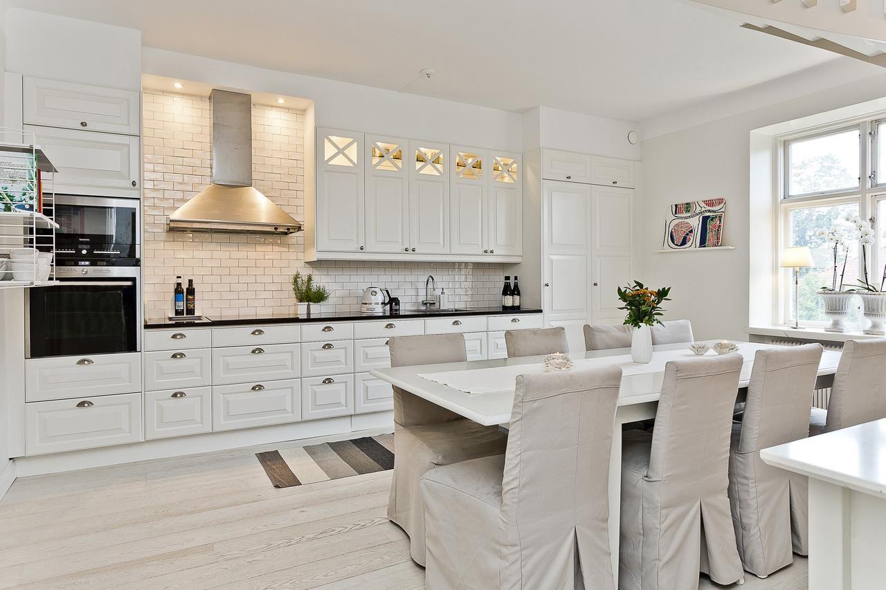 Kök från Ballingslöv i ljus lantlig stil med vitrinskåp, svart granitbänkskiva och vitt kakel