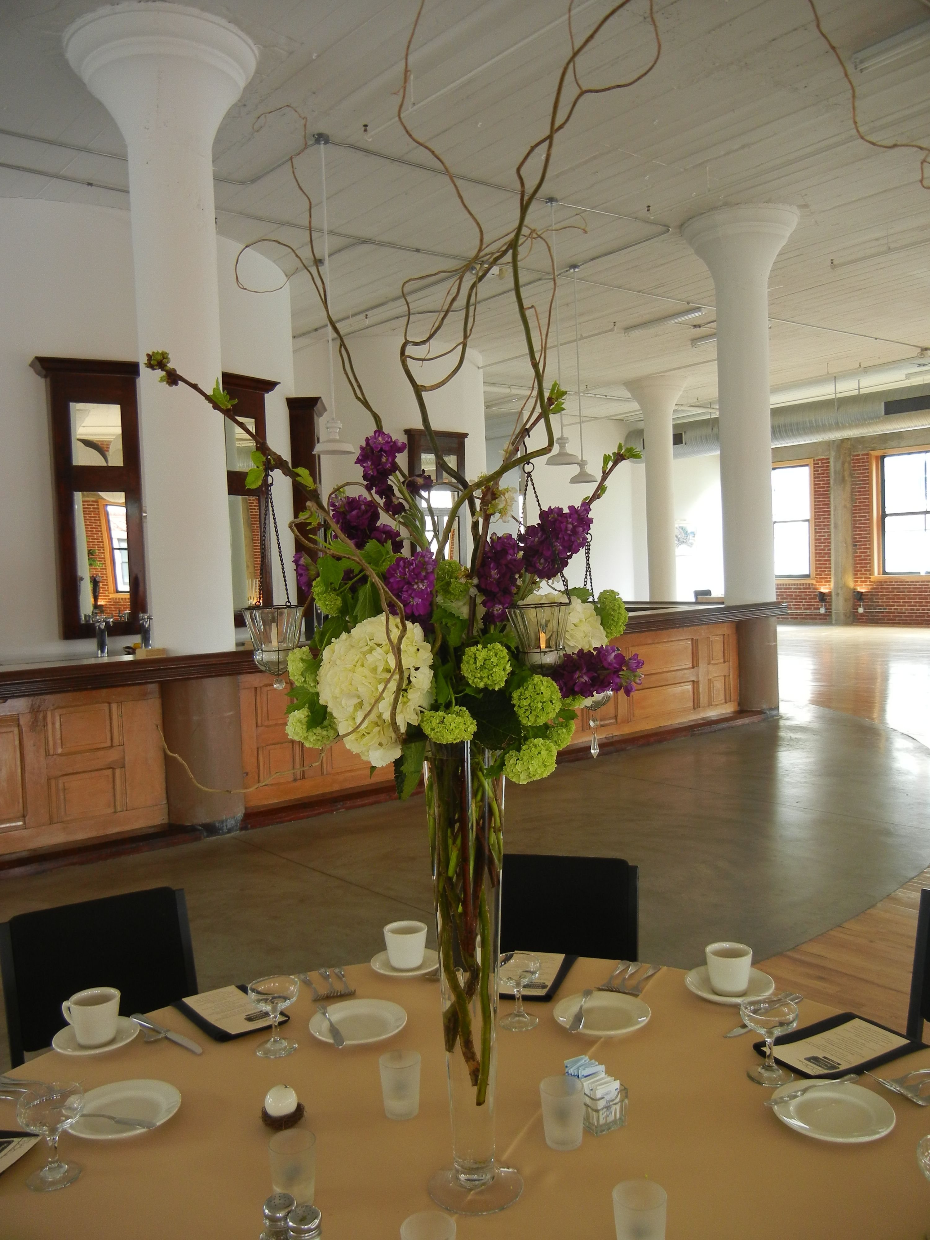 Tall centerpiece of white hydrangeas purple stock and