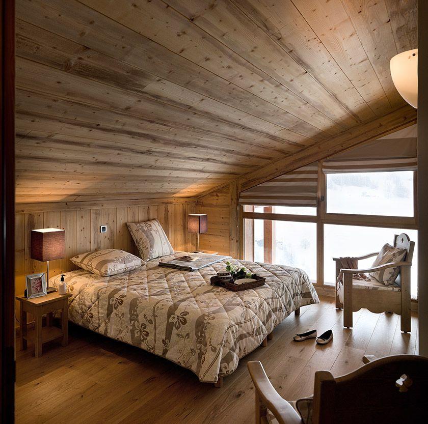 Chambre chalet sous les toits  sous les combles Grande baie vitre fauteuil bois lambris