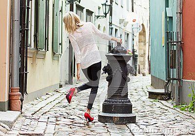 Mujer luce sus zapatos rojos, de tacón alto, en una calle de la ciudad.