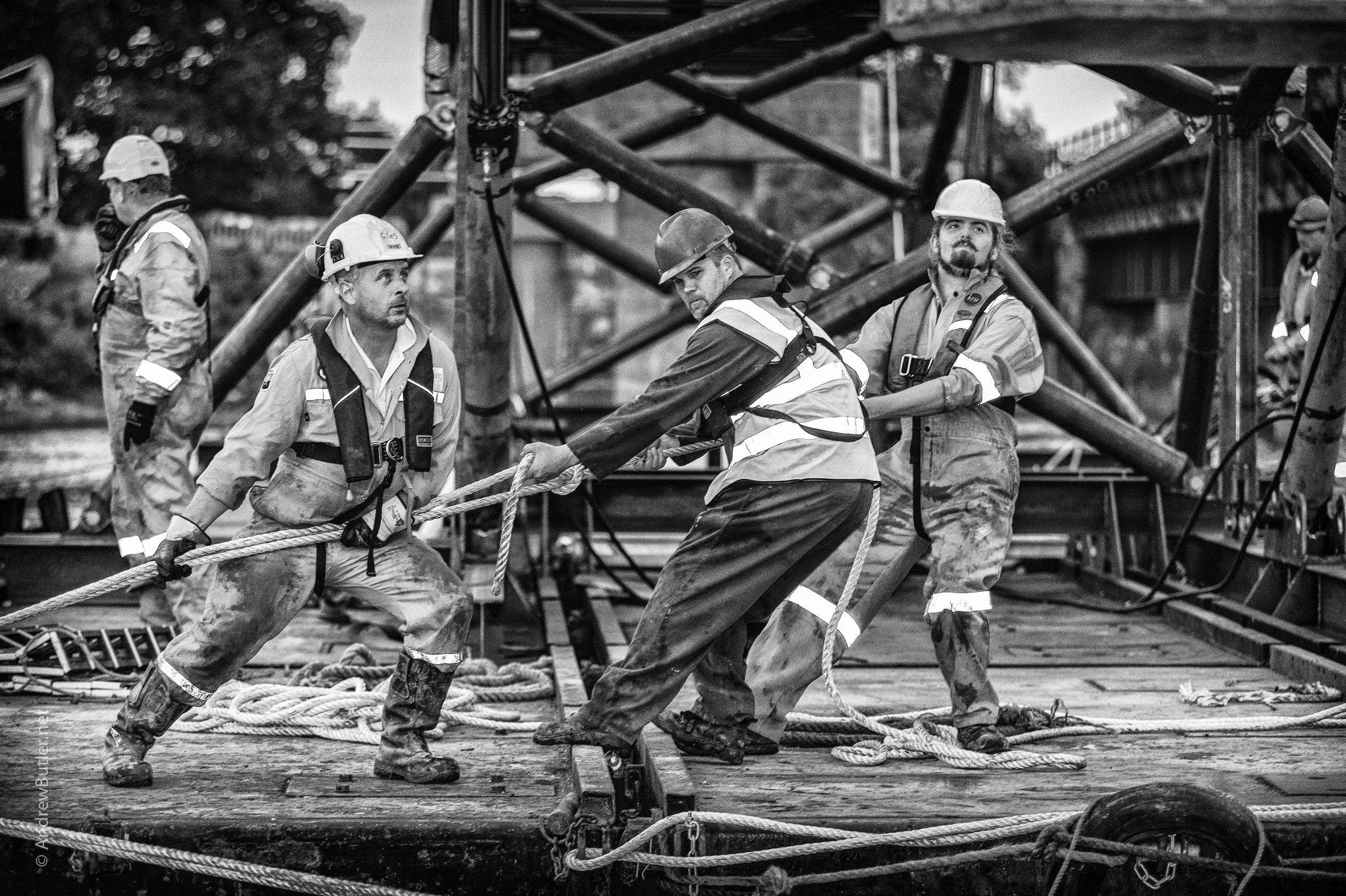 This photograph is a black and white of engineers workers working on a bridge what is captured in this photograph is the hard work and dedication people