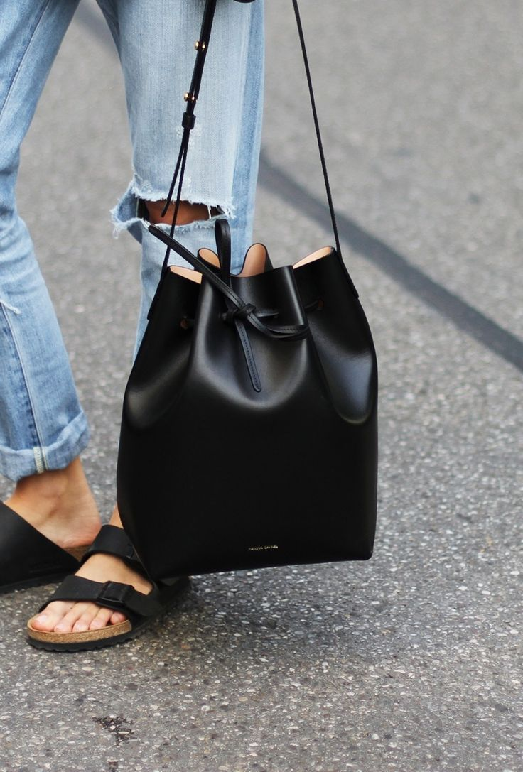 Gavriel Mansur black bucket bag, ripped boyfriend jeans + Birkenstock style slippers.