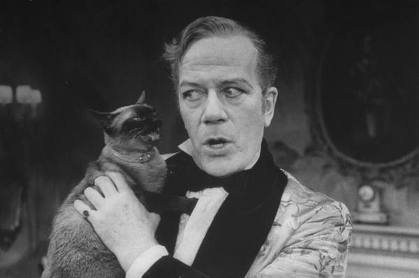 Actor Cyril Ritchard holding siamese cat