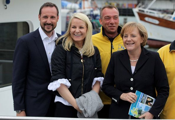 Princess Mette-Marit of Norway (C), Prince Haakon of Norway and German Chancellor Angela Merkel pose with sailors after returning from a boat trip to see nearby chalk cliffs in the Baltic Sea on June 12, 2010 in Sassnitz, Germany. The Norwegian prince and princess are on a one-day visit to northern Germany.