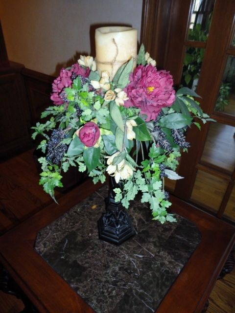 Pedestal candle holder with flowers.