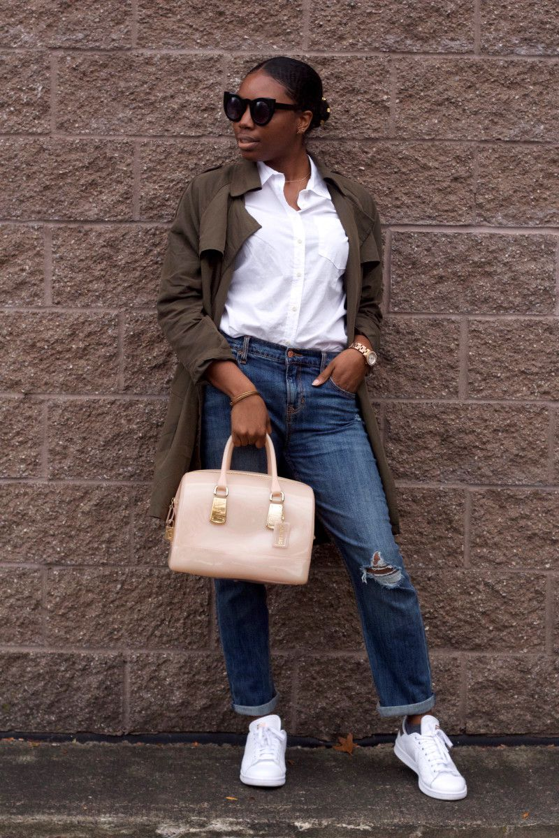 c0a3304851cf7 Amani wears a white button-up blouse tucked into loose-fit medium-wash  distressed boyfriend jeans with an olive green duster rain jacket and white  sneakers.
