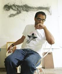 Christopher in his studio with art on his walls. he is looking into camera in tshirt and jeans