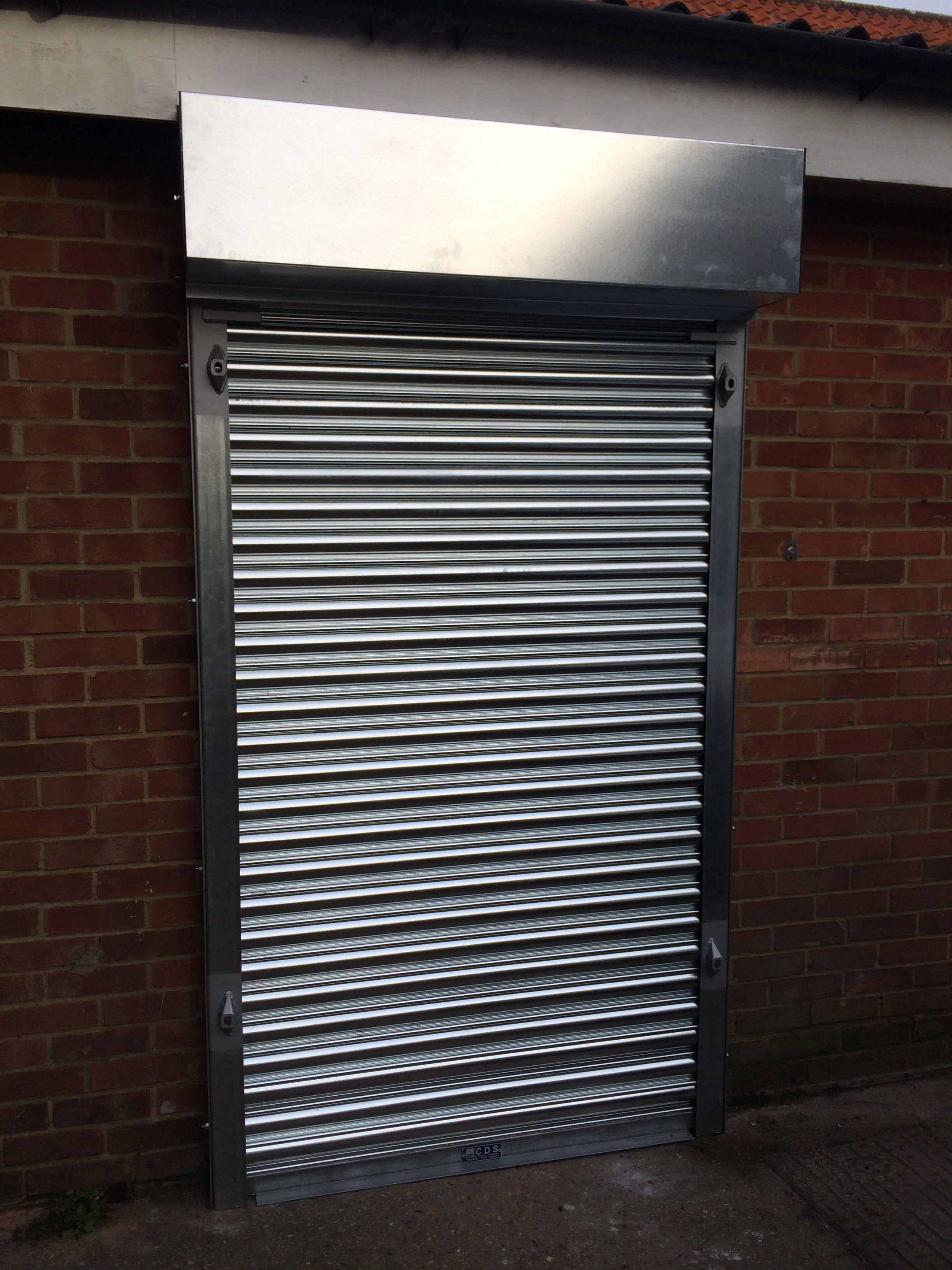 Exterior: Electric Galvanised Roller Shutter Over A Door Way