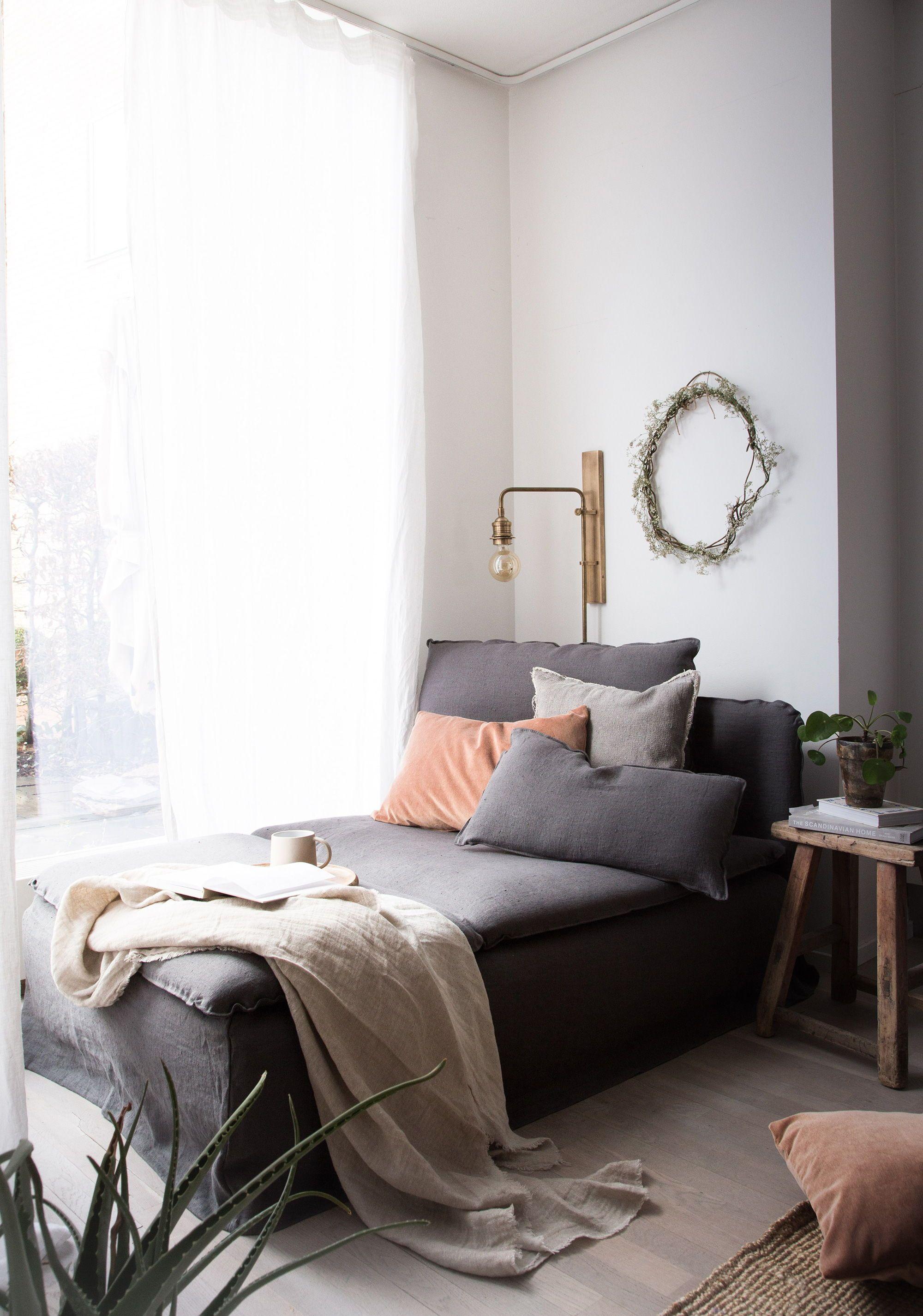 Cozy minimalist corner grey linen sofa velvet cushion covers moody pastel shades natural light light wooden floors ikea söderhamn chaise
