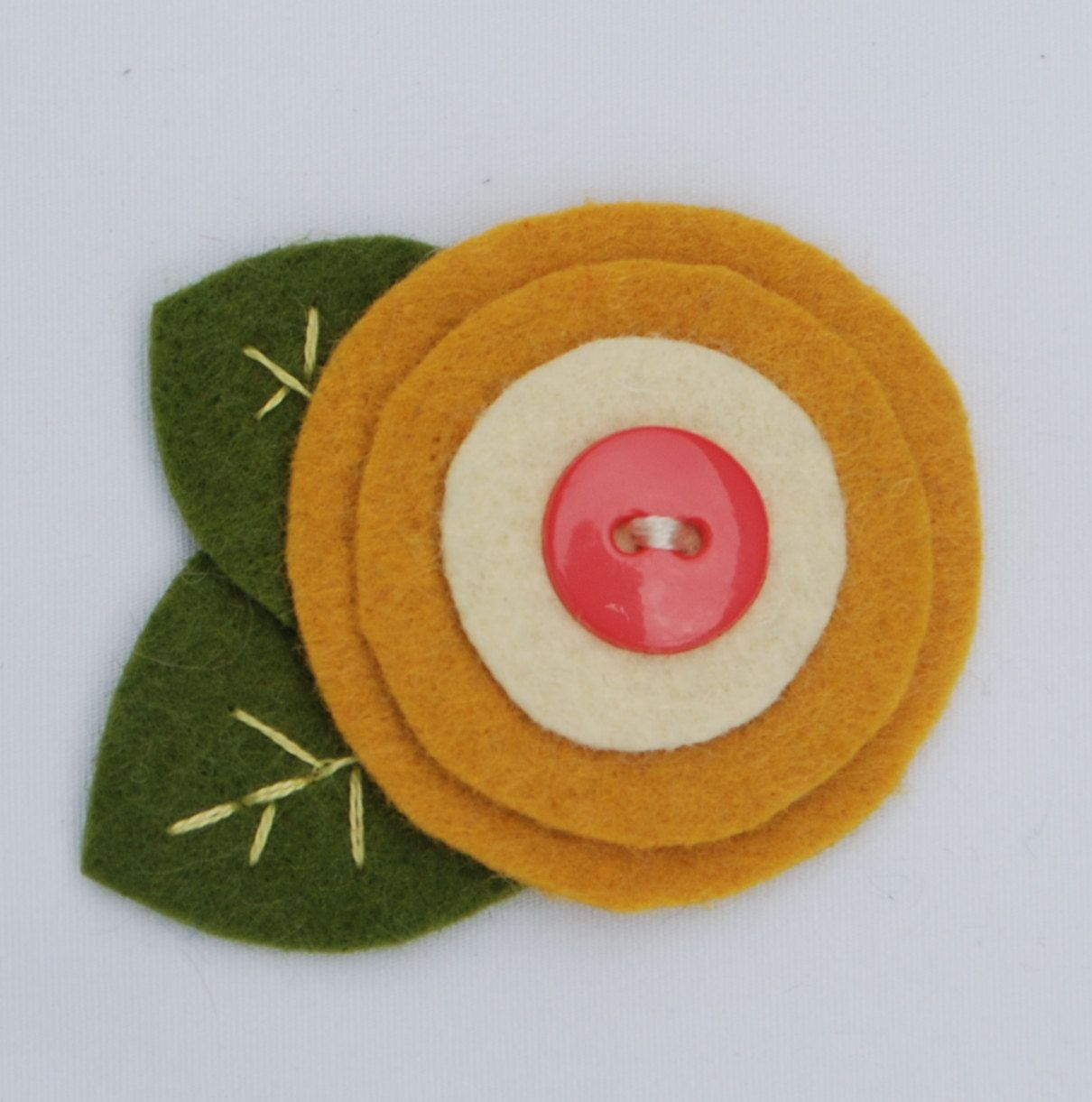 Wool Felt Flower Clip - Funky Circle & Button Flower - Ivory and Gold. $6.50, via Etsy.