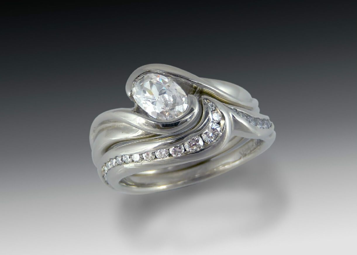 Oval Byp Bridal Set Diamond Engagement Ring In White Gold With An Shaped Stone At Angle A Carved Partial Bezel Matching Wedding Band Is