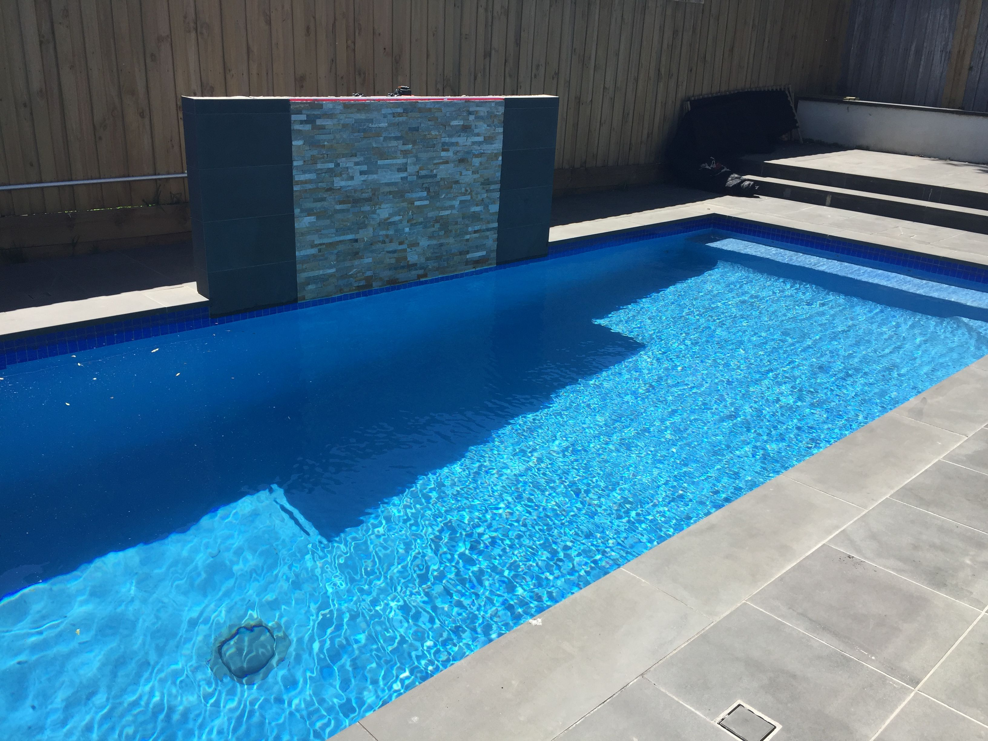 Glass waterline tiles pool with royal blue rendered interior ...