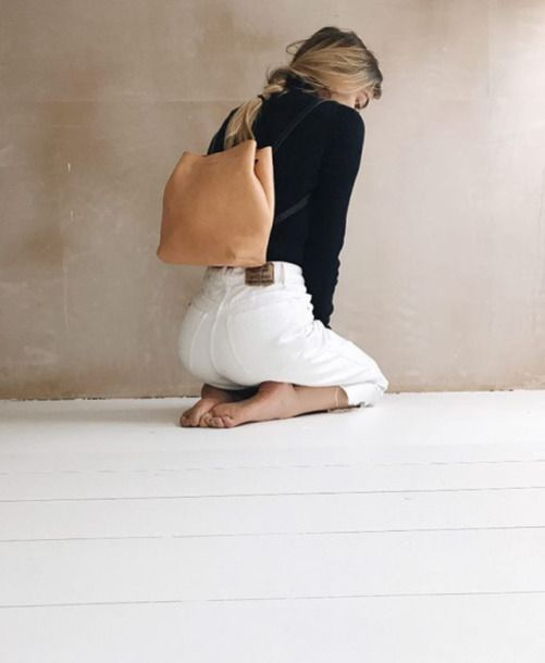 Simple Minimalist Monochrome Outfit White Mom Jeans With Black Top And Brown Orange Leather Backpack Summer Trends