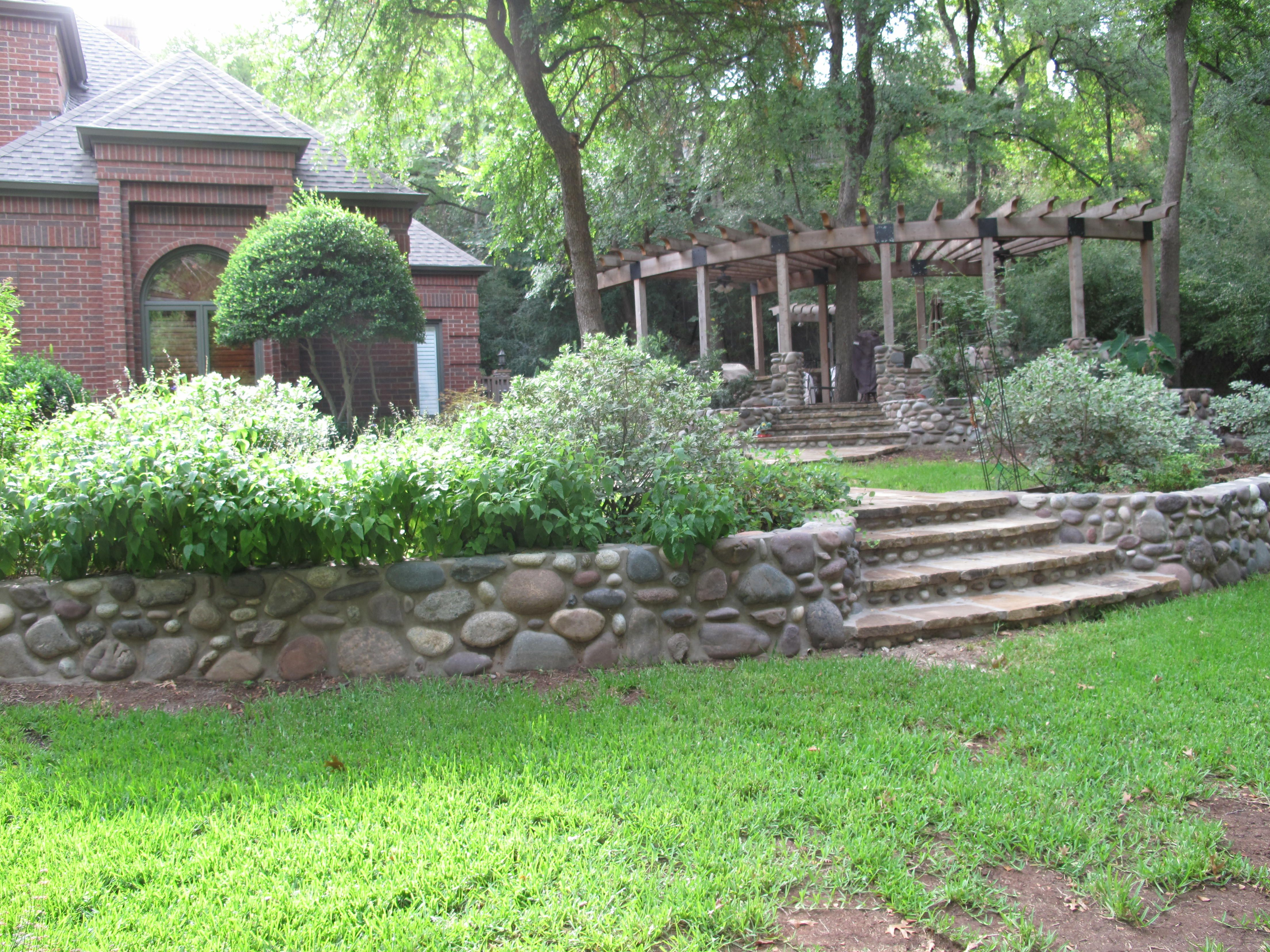 We Terraced This Hill Side With River Rock As Well As The Foundation To The Grill And Patio Area We Farmhouse Landscaping Outdoor Living Space Outdoor Living