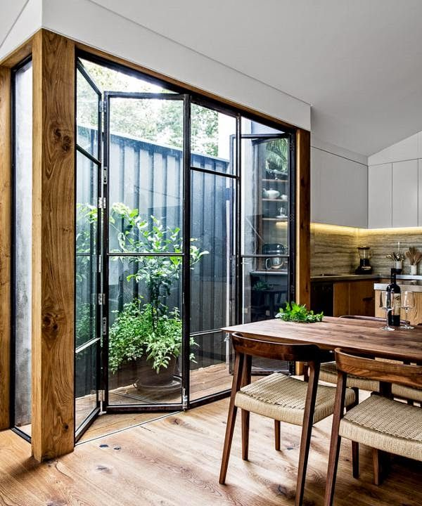 Ander voorbeeld van vouwdeur. Mooi contrast van staal met hout.  black edge bi-fold glass doors.