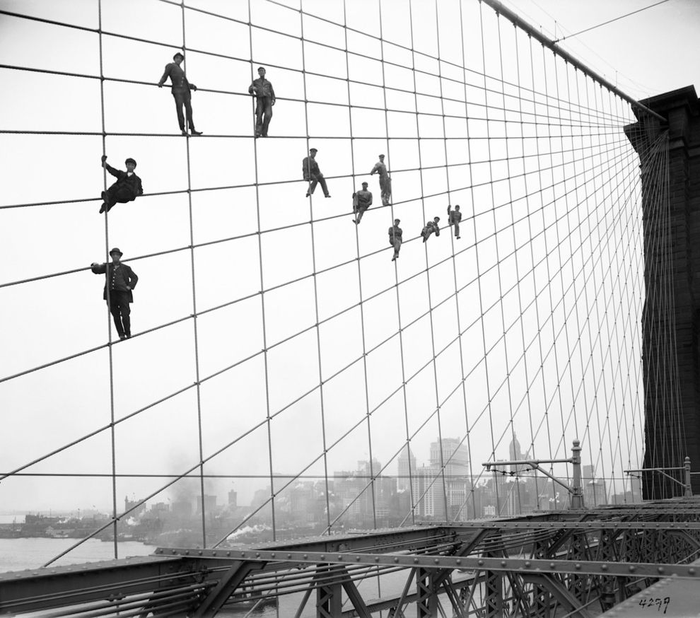 Oct. 7, 1914 photo provided by the New York City Municipal Archives, painters are suspended from wires on the Brooklyn Bridge in New York.