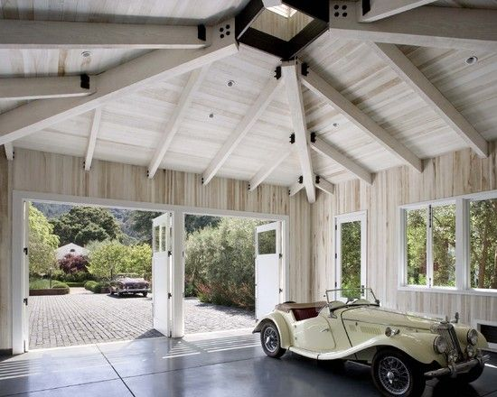 Garage with high white washed ceilings and doors that open outward ...