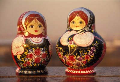 Matryoshka dolls can be elaborately painted. These floral-themed matryoshka dolls have been given arms and hands and delicately rendered jewelry. The doll on the left sports a lace bib. The doll on the right toys with her shawl.