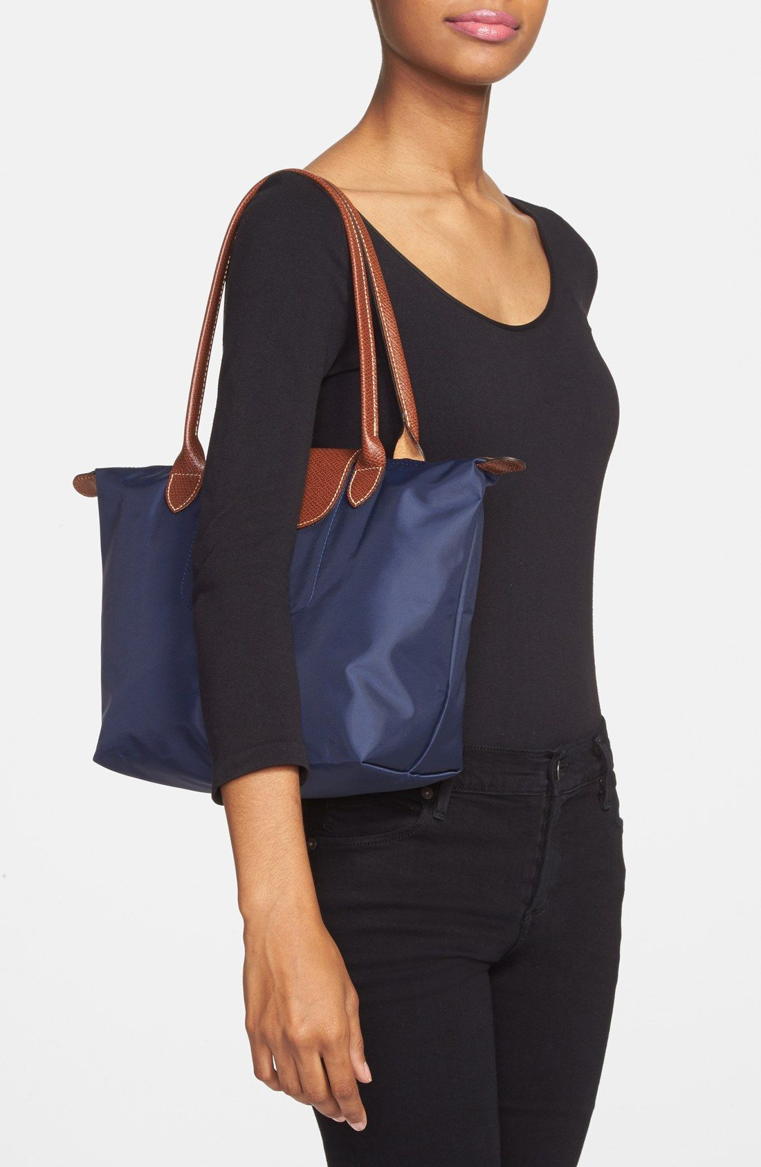 3cd936a3f Durable, water-resistant nylon fashions a right-size tote trimmed in richly  embossed leather. Snaps allow the bag to be folded into ...