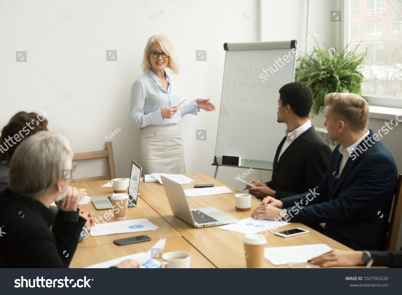 Senior Woman Boss Leading Corporate Team Meeting Presenting Team