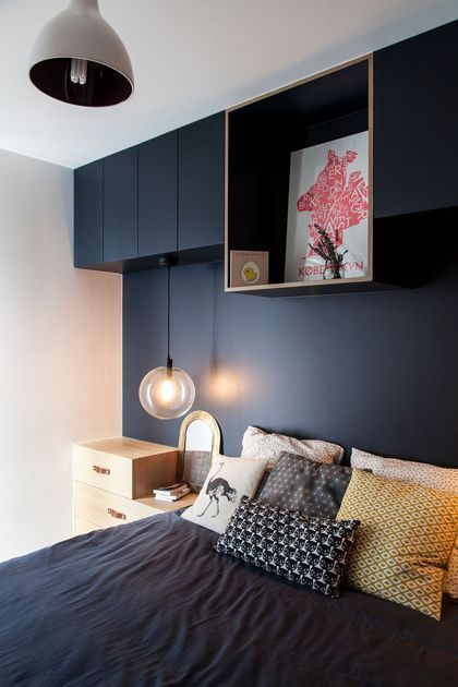 a bed under a blue alcove night in this beautiful room  colorful cushions and round suspension