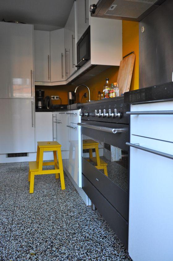 Moderne witte keuken met gele muur na STIJLIDEE Interieuradvies en Styling via www.stijlidee.nl