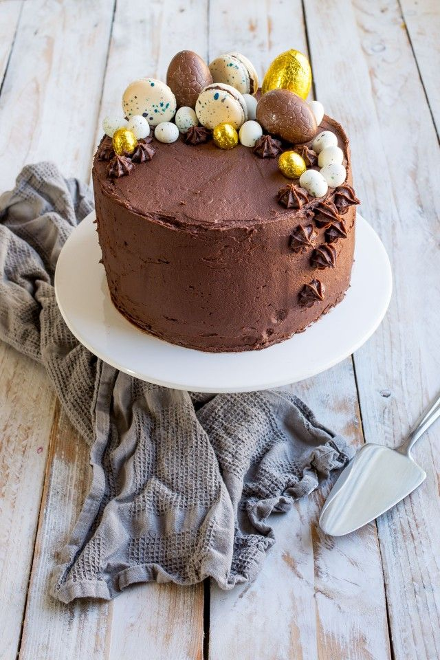 This recipe for an indulgent, moist vanilla layer cake covered in chocolate orange frosting is definitely a treat! Topped with chocolate eggs and macarons, this cake is a real show stopper!