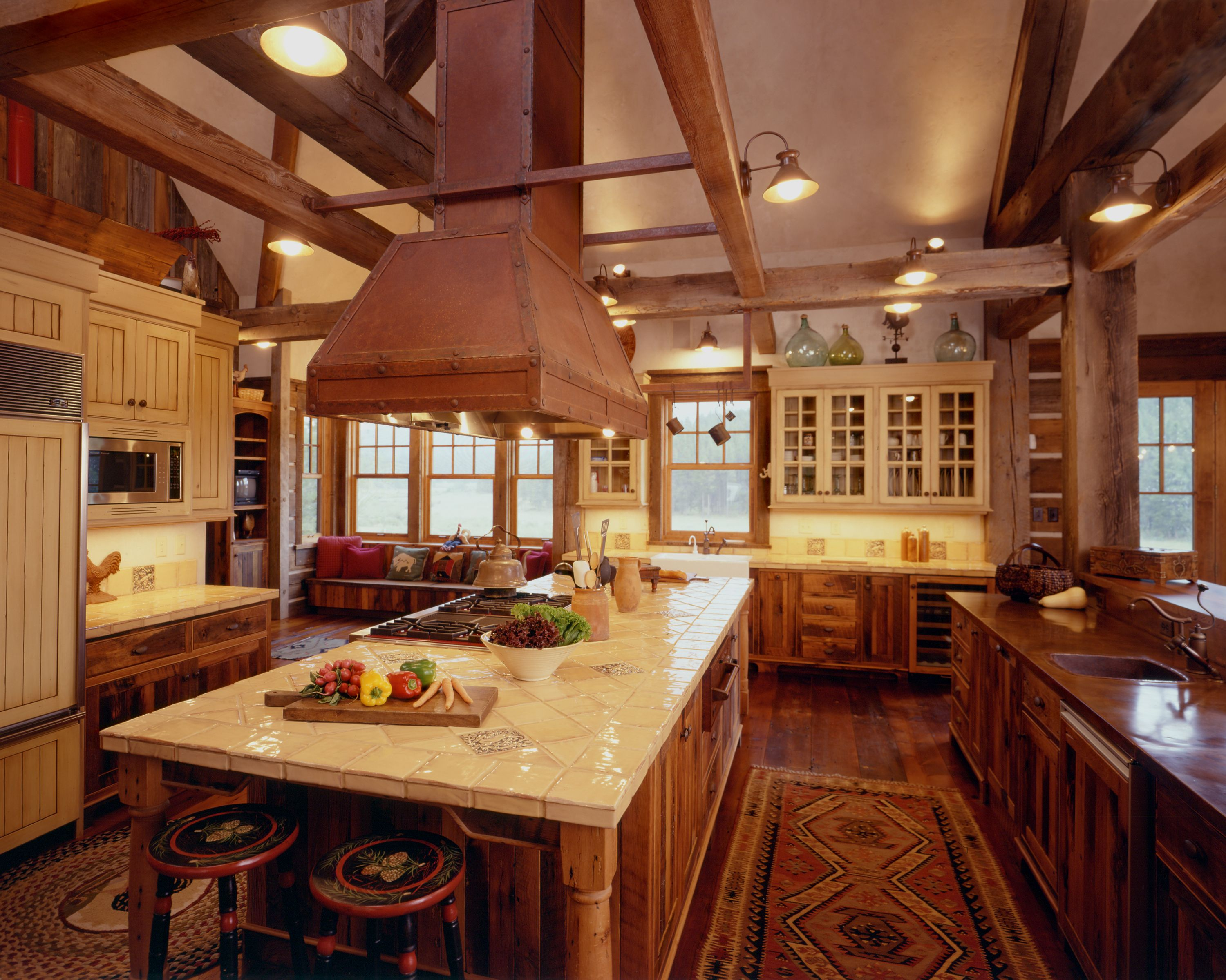 mediterranean kitchen with hand painted tile countertops and range in center island