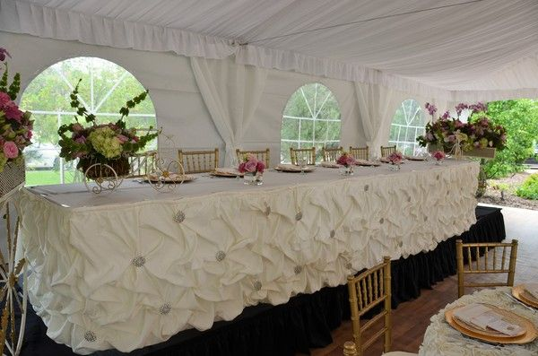 Fairy Tale Tents & Events - Frankfort, IL - 40'x40' High-Peak Fairy Tale Frame Tent with white full gathered tent liner, cathedral window side walls, white side pole swags with white ties, and full tent flooring; 12 person head table on risers with ivory lamour satin gathered skirting with brooches