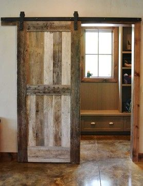 Sliding barnwood door to separate the mudroom from the rest of the home, custom made by Burchette. Stained concrete flooring with sawn grooves. The Hennek Residence by Resort Custom Homes on Houzz.