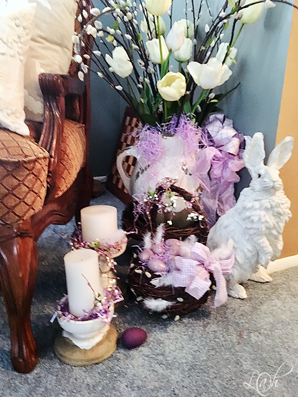 As I do love purple and I like to add it in where ever possible. In this Tuscan vase I have tulips and pussywillows. The basket also has some pussywillows poking through and some white feathers. The lilac eggs in the basket are sitting on a bed of matching grass which is also sticking out of the Tuscan vase. There is some grass and feathers around the candle holders. Here on the chair the fur …