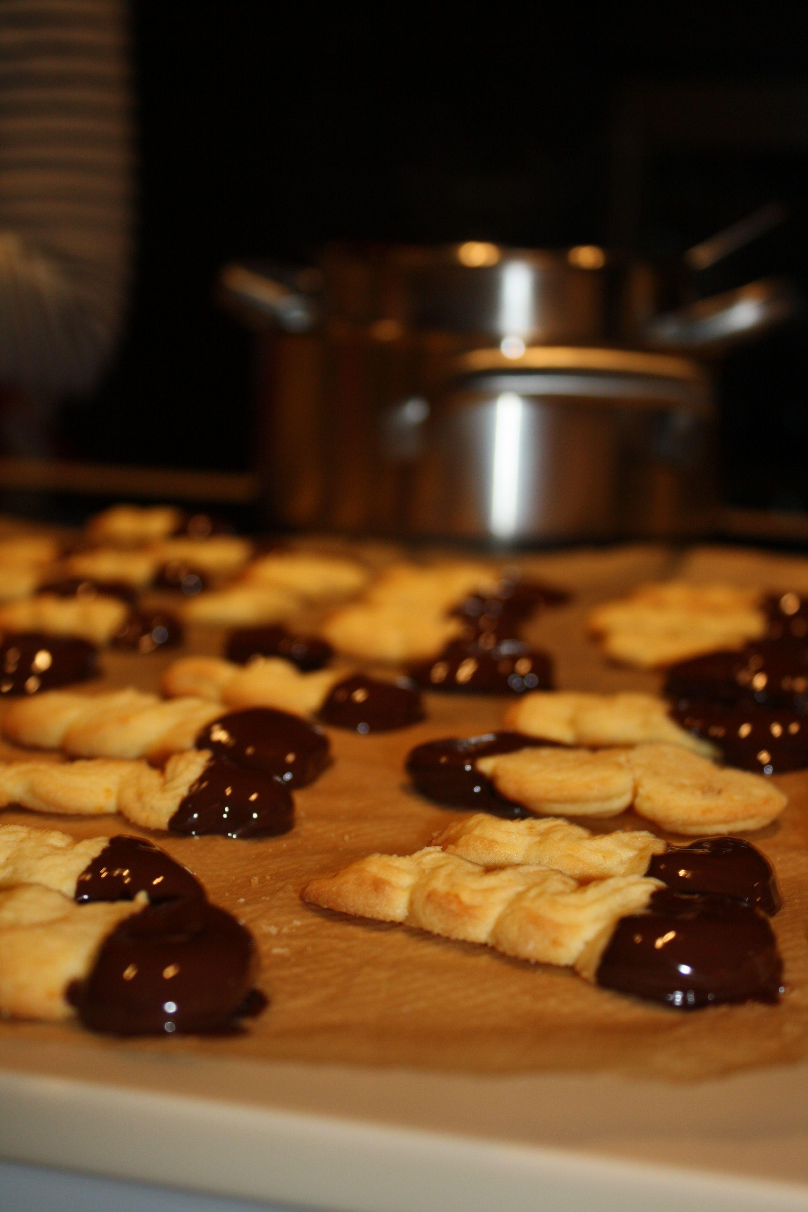 """Orangenzungen -  200g Butter mit 125g Zucker schaumig schlagen. Schale und Saft von 2 Orangen, 3 Eigelb und nach Geschmack ½ Flasche Orangenaroma nach und nach unterrühren. 100g Speisestärke und 200g Mehl einsieben.  Teig mit einem Spritzbeutel in etwa 4 cm lange """"Zungen"""" spritzen.   Im vorgeheizten Ofen bei 190°C ca. 10-12 min hellgelb backen.   200g Zartbitter-Kuvertüre im Wasserbad schmelzen und die Orangenzungen an einer Seite eintauchen, unten leicht absteifen und fest werden lassen…"""