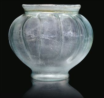 A ROMAN BLUE BLOWN GLASS JAR 1ST-2ND CENTURY A.D., FOUND AT ST. ALBANS The bulbous body with 15 moulded vertical ribs finished by tooling, the base kicked-in, the short everted neck folded outwards, 5½ in. (14 cm.) high