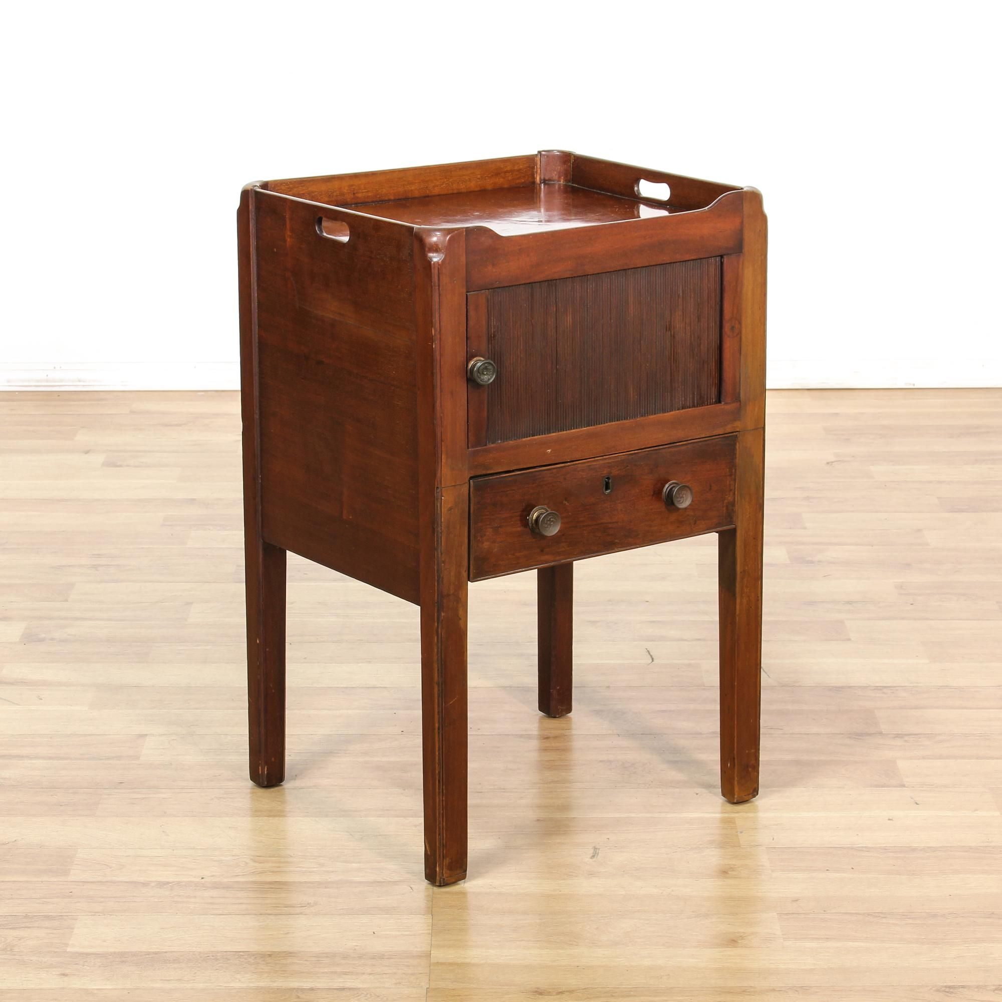 This antique Georgian style commode is featured in a solid wood with