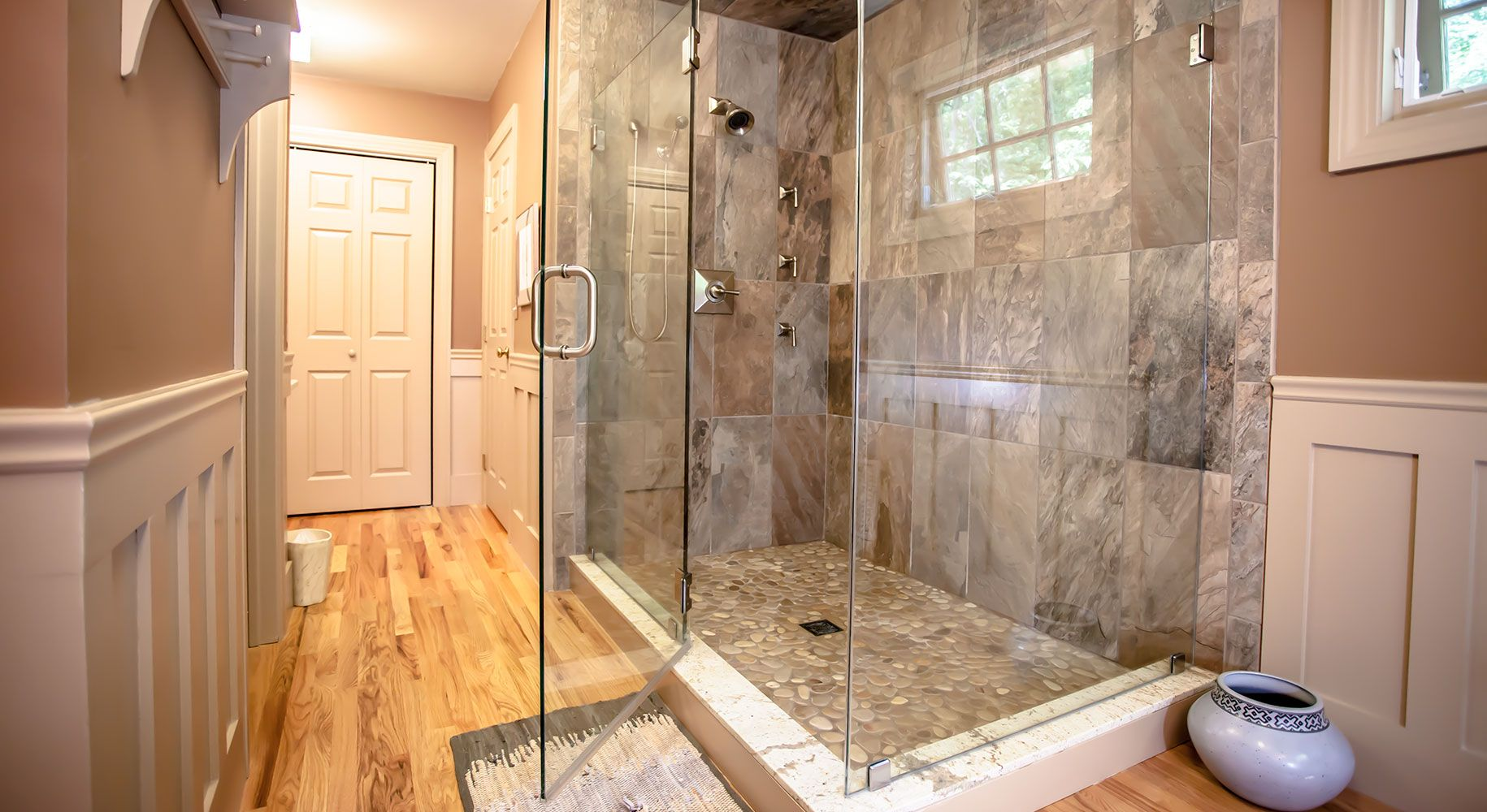 Torrco design consultants helped the homeowners bring their love of the outdoors indoors – with a glass-encased shower where natural light cascades onto a fine stone ground.