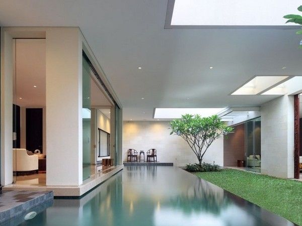 Open plan connecting roof with punctures for light over a large water body house in jakarta for Indoor swimming pool in jakarta
