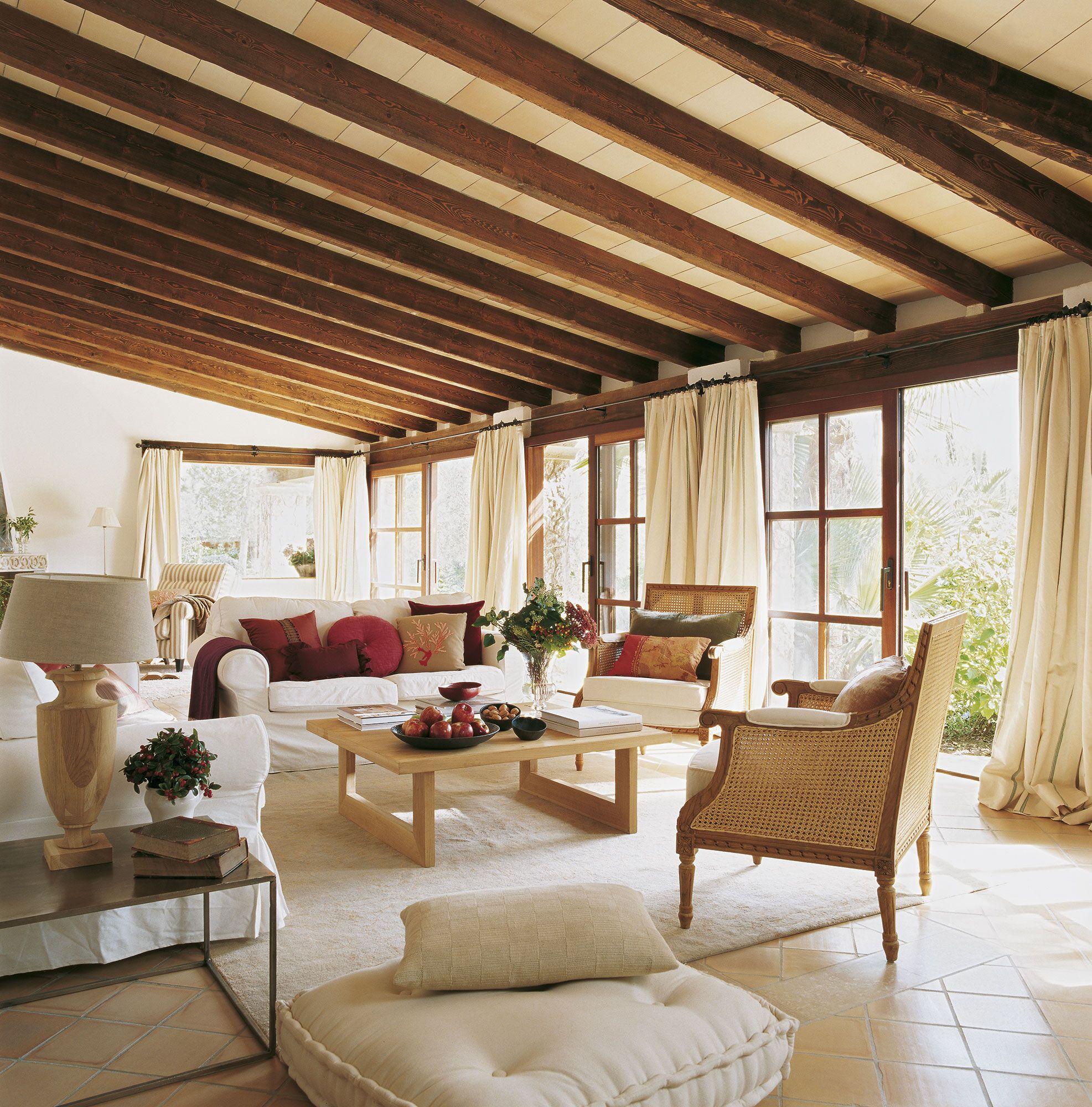Salón con suelo de terrazo, techo abuhardillado y pared de cristal ...