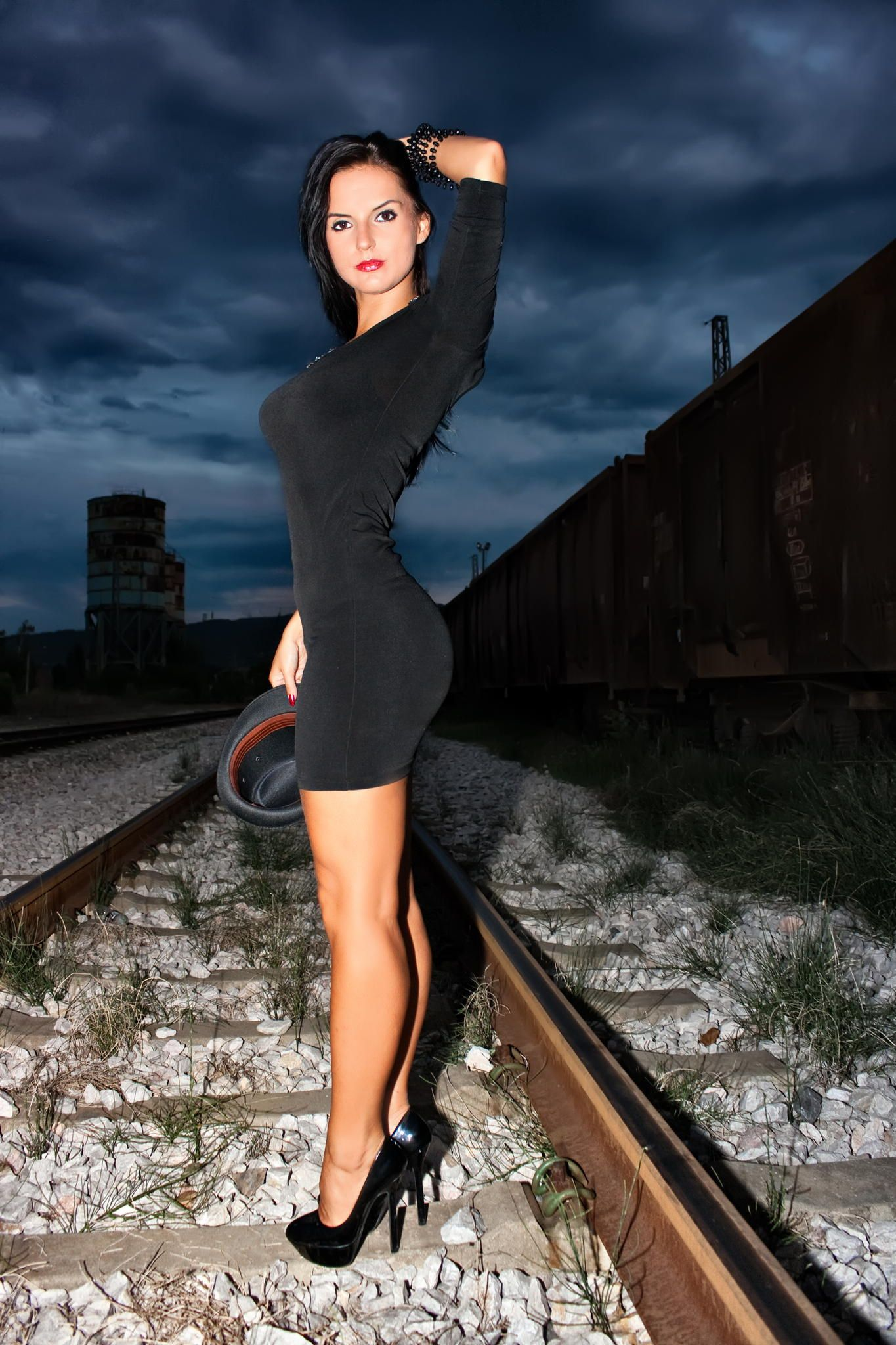 Beautiful Young Woman In A Black Dress On A Railway Line