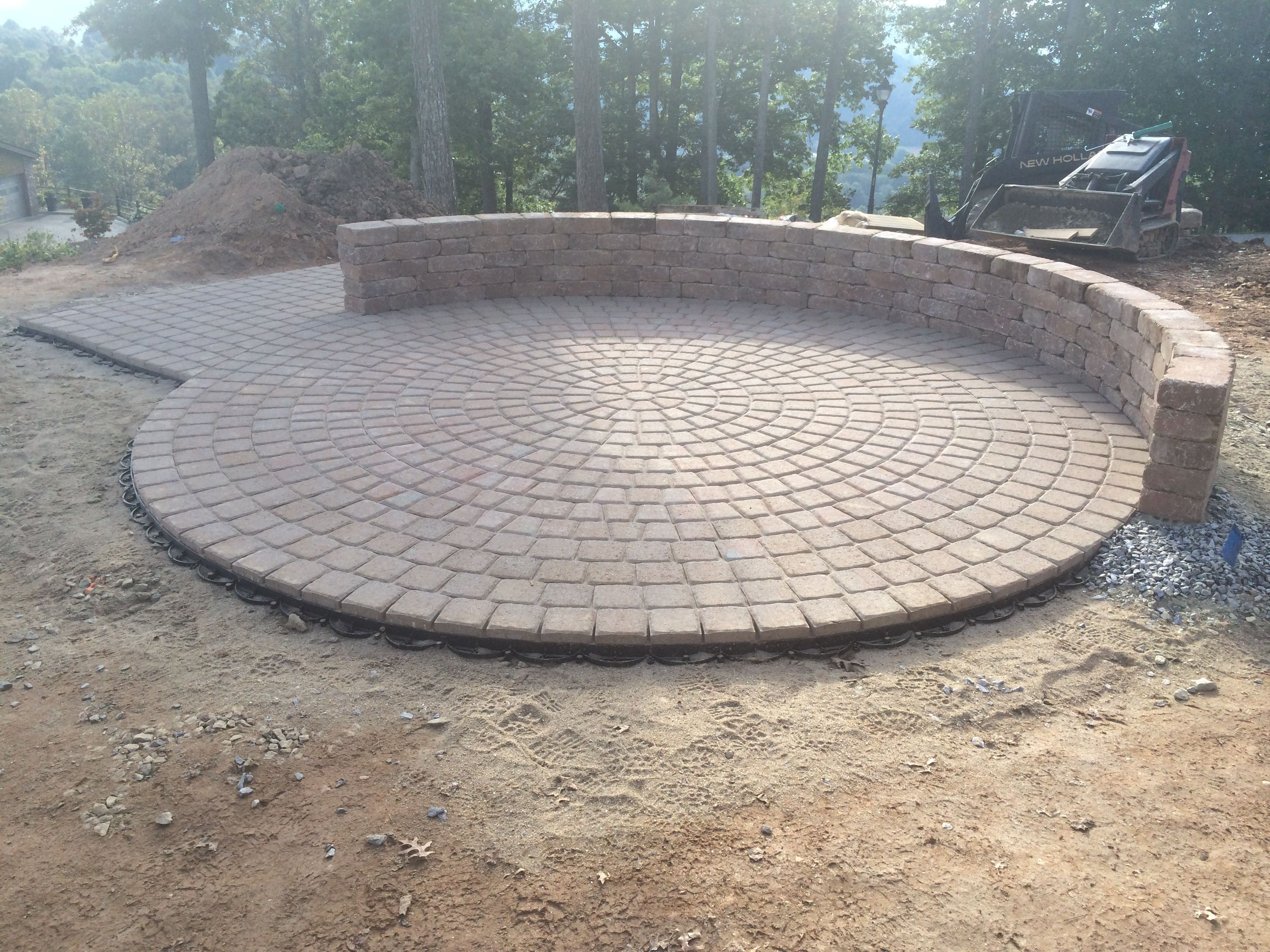 A Circle Shaped Concrete Paver Patio, With Attached Semi Circular Seating  Wall. By