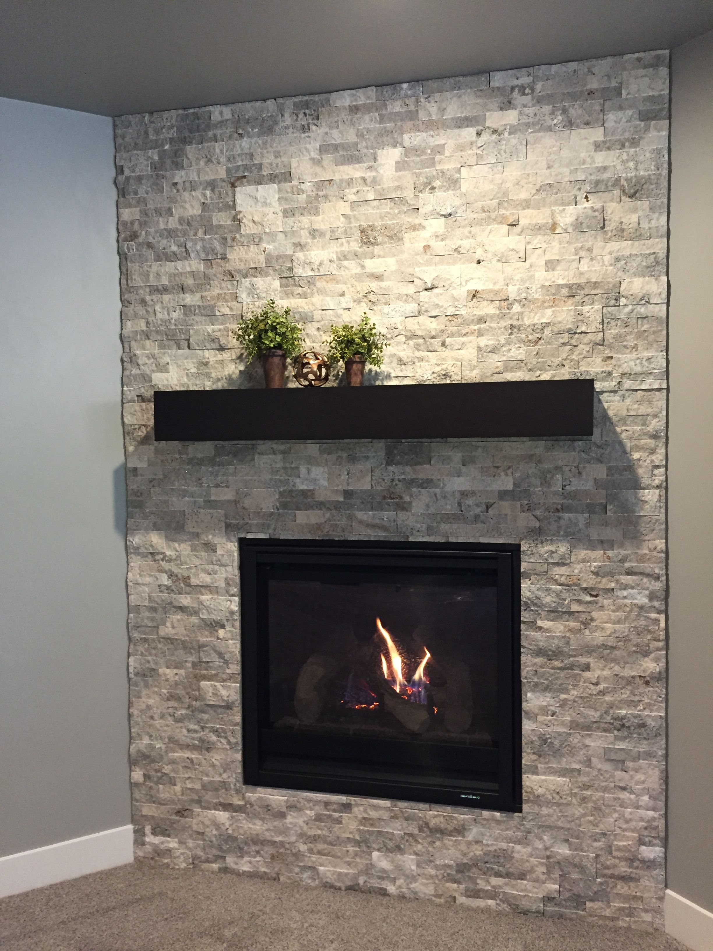 Corner Fireplace With Silver Travertine Stacked Stone Surround And