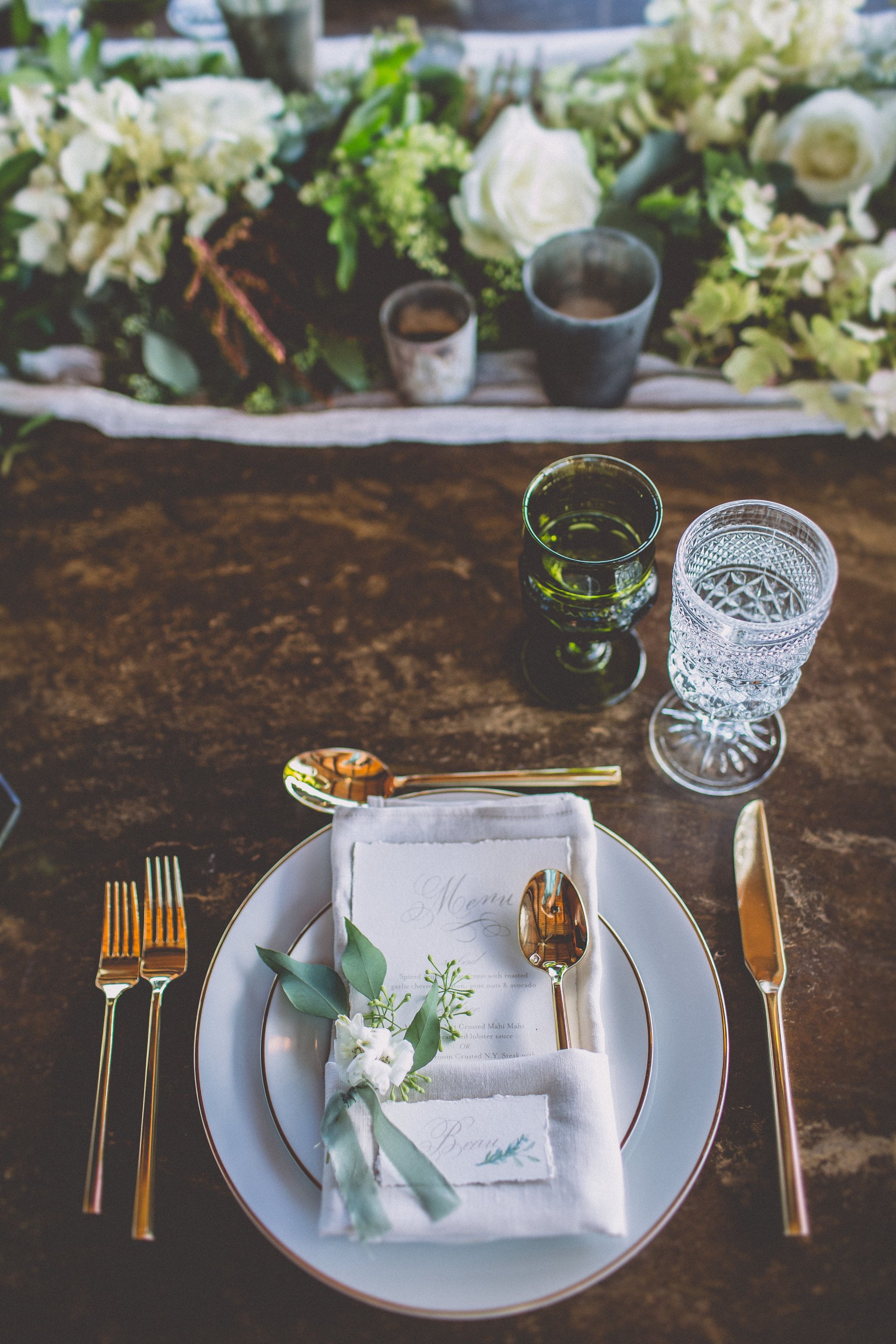 Love Green glass. Wood table. White dishes. Gold cutlery