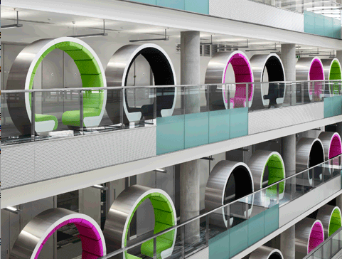 Circular meeting pods line the glass interior walls of the BBC North