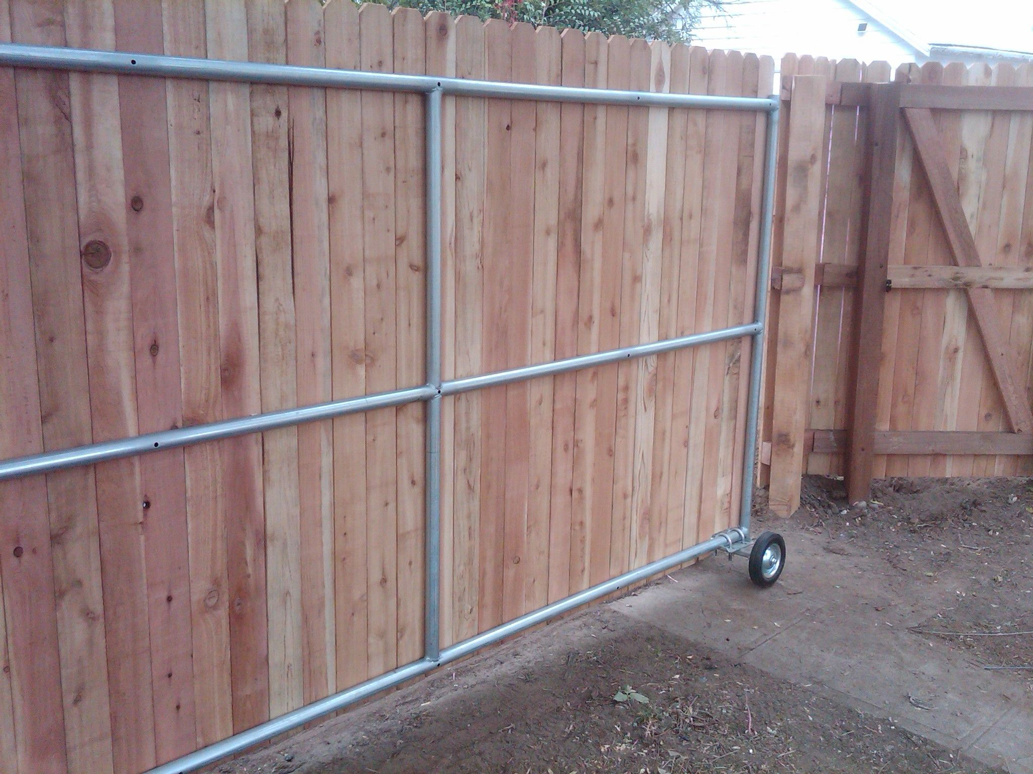 Wood fence ideas with a gate steel framed roll gate with for Wooden sliding driveway gates