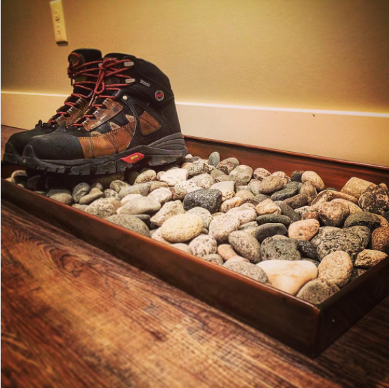 Buy a cheap wooden tray (stain it if you want), fill it with rocks, and use it to hold wet or dirty shoes by the door.